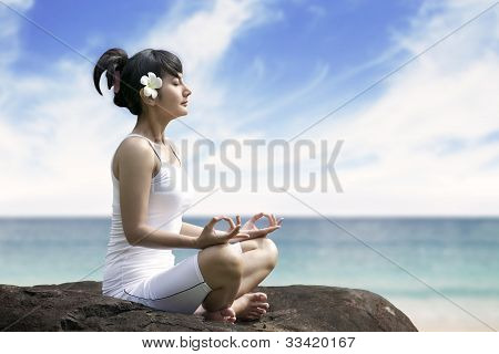 Beautiful Woman Meditating By The Sea