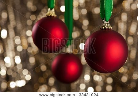 Three Red Christmas Baubles In Front Of A Gold Glitter Background