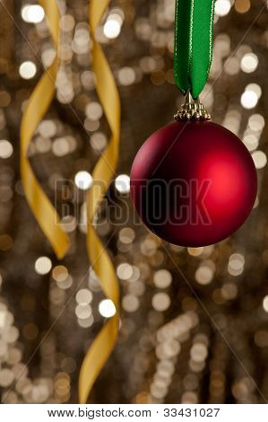 Single Christmas Bauble In Front Of A Gold Glitter Background