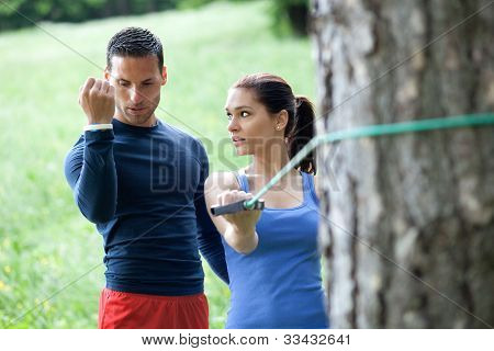 Perosonal Trainer Working With His Client, Showing Her How To Properly Execute The Exercise With Res