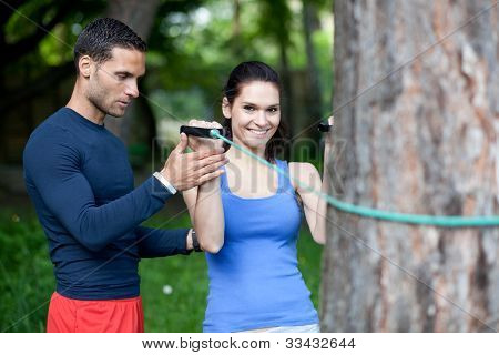 Personal Trainer Showing His Client How To Properly Execute Biceps Exercise With Resistance Band