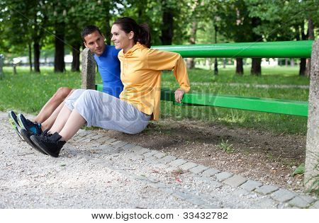 Happy Young Couple Exercising Outdoors, Using A Park Bench To Do A Triceps Exercise