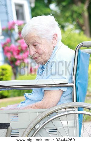 Senior Lady In Wheel Chair In Front Of House
