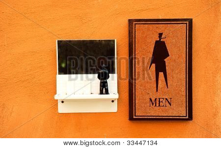 Men's toilet sign on the orange vintage wall