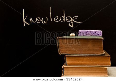 """knowledge"" Written On Blackboard With Old Books"