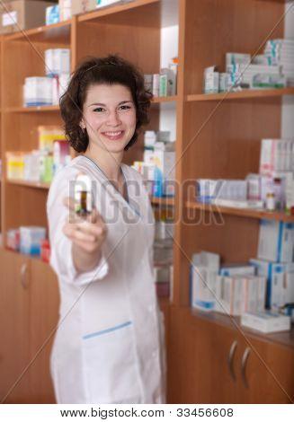 Jovem químico mostrando o frasco de comprimidos