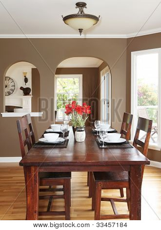Dining Room With Brown Walls And Wood Table.