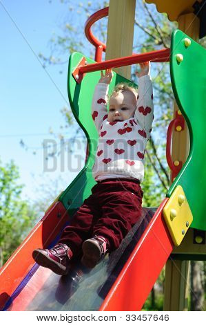 Little Girl Sliding On Playground
