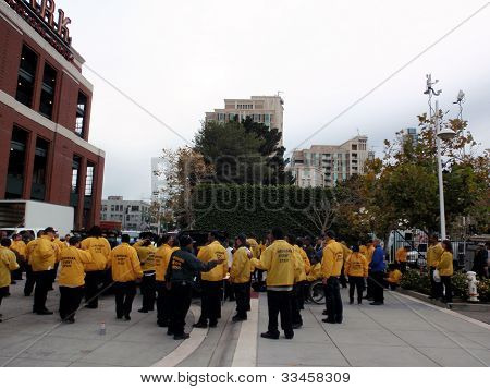 Security Staff Gather Outside Ballpark Wearing Yellow Rain Jackets As They Prepare For Event