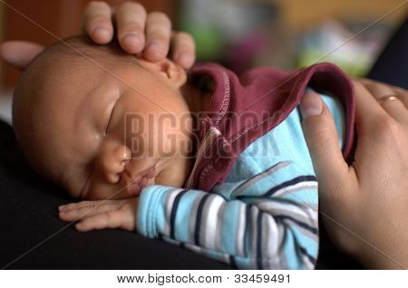 Baby sleeping in father's arms