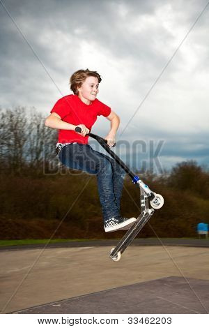 Young Boy Enjoys Riding A Scooter In The Skate Park