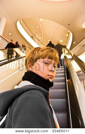 Child On Moving Staircase Looks Self Confident And Smiles