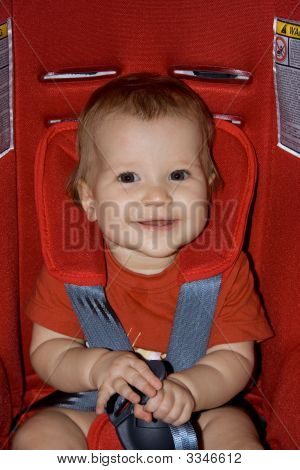 Beautiful And Happy Baby Girl In A Red Car Seat Ready For A Safe Ride.