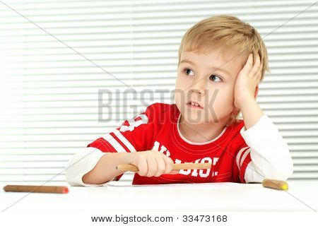 A Little Boy Sitting With A Pencil