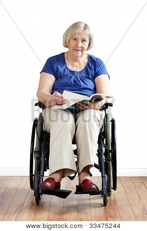 Senior Disabled Woman In Wheelchair With Book