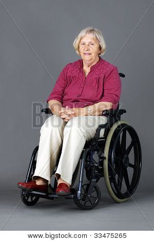 Senior Woman In Wheelchair Over Grey