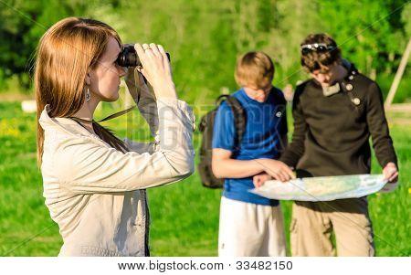 Three Friends Traveling. Girl Looking Through Binoculars