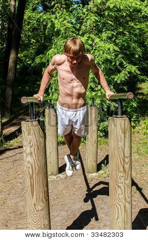 Attractive Man Pull-ups On A Bar In A Forest