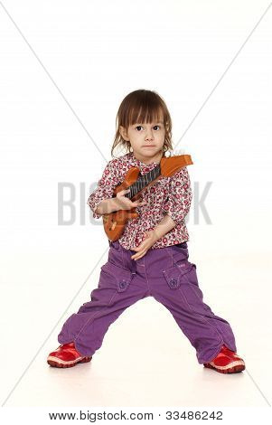 Happy Little Caucasian Girl Plays With A Guitar