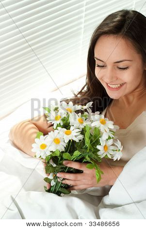 Young Caucasian Woman Sitting In Bed With Flowers