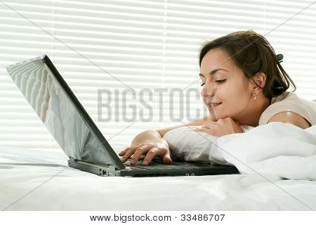 Young Caucasian Woman Lying In Bed With Laptop
