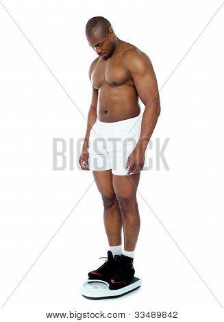 Atleta medir seu peso na máquina de pesagem
