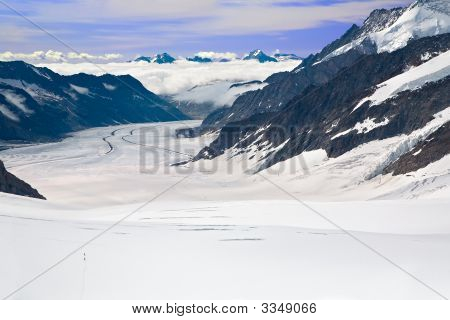 Two Hikers Walking Towards The Aletsch Glacier In The Alps, Switzerland