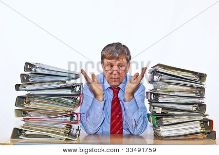 Man sitting between Folder With Files At His Desk In The Office