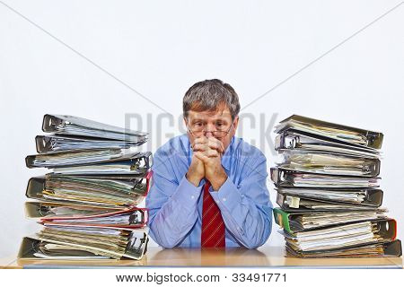 Man between Folder With Files At His Desk In The Office