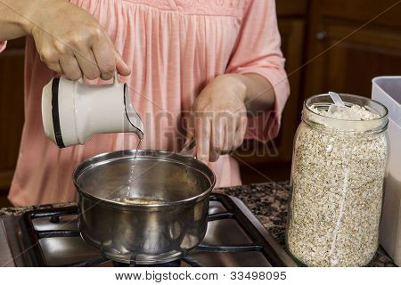 Making Breakfast With Adding Water To Oatmeal On Stove Top