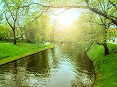 Boat Tour On River Or Canal In City Park Among Green Spring Trees. Landscape Of River With Tourist B poster