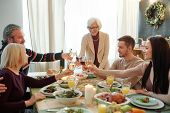 Young and senior members of big family clinking with glasses of wine over served festive table durin poster