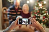 Hands of man holding smartphone while taking photo of big relaxed family by festive dinner on Christ poster