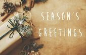 Seasons Greetings Text Sign On Stylish Rustic Christmas Gifts Box With Cedar Branch On Rural Table  poster