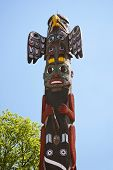 stock photo of indian totem pole  - Totem pole on blue sky background and green tree - JPG