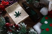 Eco Paper Pack With Green Marijuana Sign With Christmas Symbol Background Closeup. Legal Drug Concep poster
