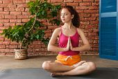 Photo of a beautiful concentrated young fitness redhead woman meditate indoors over brick wall and t poster