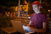 Smiling teenage boy typing message on smartphone. Handsome young man with notebook, outdoors. Cheerf poster