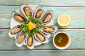 Mussels With Herbs With Lemon Parsley In The Table / Steamed Mussels Served On White Plate And Sauce poster