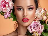Beautiful white girl with flowers. Stunning brunette girl with big bouquet flowers of roses. Closeup poster