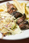 image of kababs  - pork and liver kabob shish kabab meal salad French fried potatoes as photographed in Tunis Tunisia