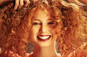Happy laughing girl enjoys her beautiful red curly hair. Close-up portrait. Hair care, hair coloring poster