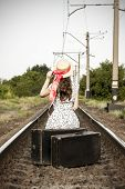 A Young Girl Sits With A Suitcase On The Railway Tracks. Beautiful Girl Is Waiting With A Suitcase.  poster