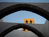 Two Gray Stone Archways With The White Stucco Walls Of Buildings Of The Greek Orthodox Monastery Of  poster