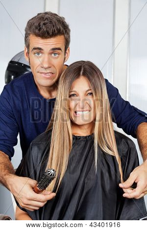 Portrait of mature hair dresser and client making faces at salon