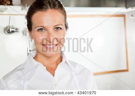 Portrait of happy female chef in industrial kitchen