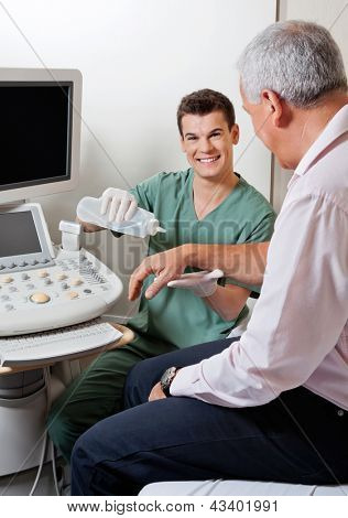 Portrait of young male radiologic technician smiling while putting gel to male patient's hand