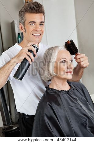 Portrait of male hairdresser with hairspray and hairbrush setting up female customer's hair at beauty salon