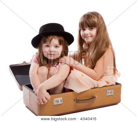 Girls Sitting In Suitcase