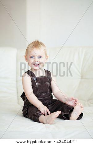 Bild eines Babys sitzen auf einem Sofa zu Hause